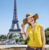 明亮的女衬衫的微笑的妇女反对埃佛尔铁塔在巴黎 图库摄影
