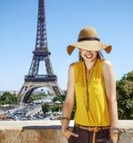 明亮的女衬衫的微笑的妇女在埃佛尔铁塔前面在巴黎 库存照片