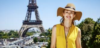 明亮的女衬衫的微笑的妇女在埃佛尔铁塔,巴黎前面 库存照片