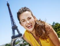 明亮的女衬衫的微笑的少妇反对埃佛尔铁塔,巴黎 免版税库存照片