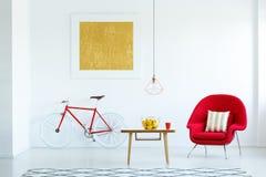 明亮的客厅内部的真正的照片与一把红色扶手椅子的, 免版税库存图片