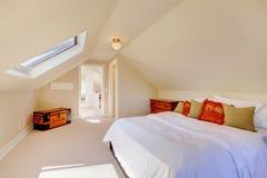 明亮的干净的顶楼卧室在小的家。 免版税库存照片