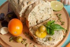 明亮的开胃构成用在一个木板,成熟黄色蕃茄,意大利面制色拉,大蒜,绿橄榄的一个家制面包, 免版税库存图片