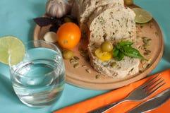 明亮的开胃构成用在一个木板,成熟黄色蕃茄,意大利面制色拉,大蒜,绿橄榄的一个家制面包, 库存照片