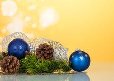 明亮的新年` s玩具球,丝带和爆沸,在黄色 免版税库存图片