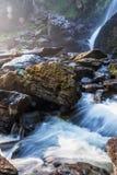 明亮的日出发光在瀑布的,轻轻地水落从在小河的峭壁的,抽象bokeh背景,Khlong Lan 免版税库存图片