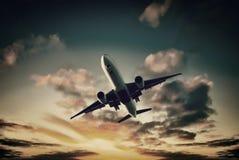 从明亮的日落天空的喷气飞机着陆 库存图片