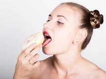 明亮的构成的女孩吃与结冰的一个鲜美多福饼 有甜点的滑稽的快乐的妇女,点心 在背景空白弓概念节食的显示评定编号附近自己的缩放比例磁带文本附加的空白视窗包裹了您 旧货 免版税图库摄影