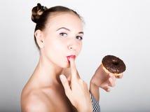 明亮的构成的少妇吃与结冰的一个鲜美多福饼 有甜点的滑稽的快乐的妇女,点心 在背景空白弓概念节食的显示评定编号附近自己的缩放比例磁带文本附加的空白视窗包裹了您 免版税图库摄影
