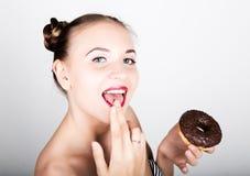 明亮的构成的少妇吃与结冰的一个鲜美多福饼 有甜点的滑稽的快乐的妇女,点心 在背景空白弓概念节食的显示评定编号附近自己的缩放比例磁带文本附加的空白视窗包裹了您 库存图片