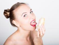 明亮的构成的少妇吃与结冰的一个鲜美多福饼 有甜点的滑稽的快乐的妇女,点心 在背景空白弓概念节食的显示评定编号附近自己的缩放比例磁带文本附加的空白视窗包裹了您 免版税库存图片