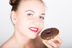 明亮的构成的少妇吃与结冰的一个鲜美多福饼 有甜点的滑稽的快乐的妇女,点心 在背景空白弓概念节食的显示评定编号附近自己的缩放比例磁带文本附加的空白视窗包裹了您 图库摄影