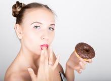 明亮的构成的少妇吃与结冰的一个鲜美多福饼 有甜点的滑稽的快乐的妇女,点心 在背景空白弓概念节食的显示评定编号附近自己的缩放比例磁带文本附加的空白视窗包裹了您 库存照片