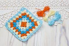 明亮的格子花呢披肩,毯子起点  钩针编织手工制造老婆婆正方形和毛线球 五颜六色的原物被编织的手工制造工作 Ho 免版税库存照片