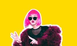 明亮的桃红色假发的酸疯狂的热的美丽的岩石在喇嘛的女孩和太阳镜用皮革包盖赃物样式红色毛皮冬天外套 免版税库存图片