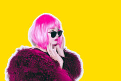 明亮的桃红色假发的酸疯狂的热的美丽的岩石在喇嘛的女孩和太阳镜用皮革包盖赃物样式红色毛皮冬天外套 免版税图库摄影