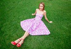 明亮的桃红色礼服的时髦的少妇坐绿色gr 免版税图库摄影