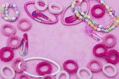 明亮的桃红色逗人喜爱的五颜六色的头发丝带、镯子和项链,发夹 少女少年样式背景 一水平的templat 免版税库存照片