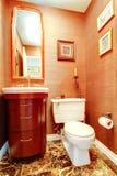 明亮的橙色卫生间在豪华房子里 免版税库存图片