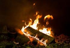 明亮的橙色火焰和被击碎的日志零件,篝火的木柴基础 库存图片