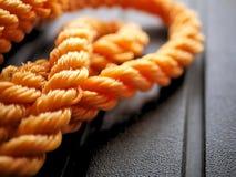 明亮的橙色结辨的尼龙绳索在被缠结的卷黑色背景中 库存照片