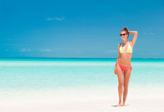 明亮的比基尼泳装的女孩走在热带海滩的 库存照片