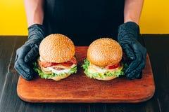 明亮的水多的开胃汉堡用炸肉排,乳酪,用了卤汁泡黄瓜、蕃茄和烟肉在女孩,一个女孩的手上s的 库存图片
