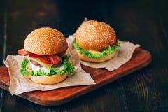 明亮的水多的开胃汉堡用炸肉排,乳酪,用了卤汁泡黄瓜、蕃茄和烟肉在女孩,一个女孩的手上s的 库存照片