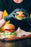 明亮的水多的开胃汉堡用炸肉排,乳酪,用了卤汁泡黄瓜、蕃茄和烟肉在女孩,一个女孩的手上s的 图库摄影