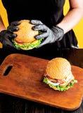 明亮的水多的开胃汉堡用炸肉排,乳酪,用了卤汁泡黄瓜、蕃茄和烟肉在女孩,一个女孩的手上s的 免版税库存图片