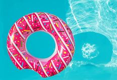 明亮的漂浮在与大海的游泳池的多福饼形状可膨胀的圆环, 库存照片