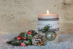明亮的灼烧的蜡烛和自然圣诞节装饰在雪 免版税库存照片