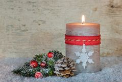 明亮的灼烧的蜡烛和自然圣诞节装饰在雪 免版税库存图片