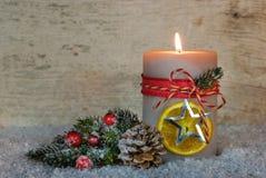 明亮的灼烧的蜡烛和自然圣诞节装饰在雪 免版税图库摄影
