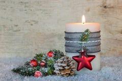 明亮的灼烧的蜡烛和自然圣诞节装饰在雪 库存照片