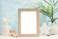 明亮的热带嘲笑与米黄照片框架、棕榈叶在花瓶和家庭装饰在蓝色背景 免版税库存图片