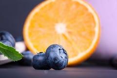 明亮的甜橙一半和越桔特写镜头 充分成熟异乎寻常的果子和五颜六色的鲜美莓果维生素用薄菏 免版税库存图片