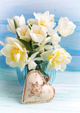 明亮的白色黄水仙和郁金香花在蓝色花瓶和deco 免版税库存图片