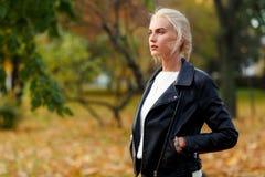 明亮的秋天树背景的沉思时髦的白肤金发的女孩  免版税库存照片
