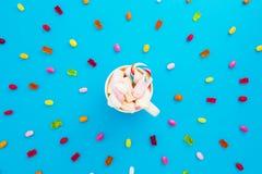 明亮的糖果和蛋白软糖在热奶咖啡在蓝色背景抢劫 平的位置,顶视图 免版税库存图片