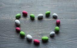 明亮的糖果在木头的心脏 库存照片