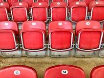 明亮的红色塑料位子在体育场内 免版税库存照片