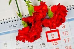 明亮的红色康乃馨花束在日历上的与被构筑的5月9日日期-胜利天明信片 免版税库存照片