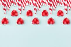 明亮的红色心脏和鸡尾酒秸杆作为装饰边界在薄荷的淡色纸背景 库存图片