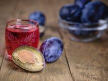 明亮的红色李子开胃酒在一张木桌上的 图库摄影