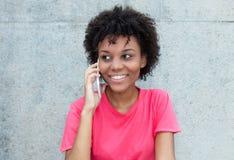 明亮的红色衬衣的巴西妇女在电话 免版税库存图片