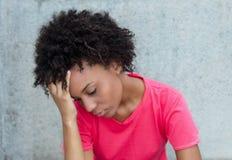 明亮的红色衬衣的沮丧的巴西妇女 免版税库存照片