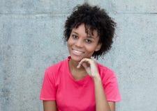 明亮的红色衬衣的笑的巴西妇女 免版税库存图片