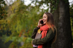 明亮的红色围巾的可爱的女孩倾斜反对一棵大树的树干 库存图片
