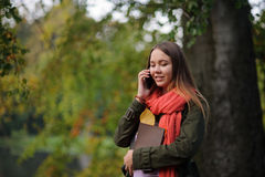 明亮的红色围巾的可爱的女孩倾斜反对一棵大树的树干 免版税图库摄影